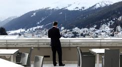 A businessman stands on a snow-covered outdoor terrace at the InterContinental hotel in Davos, Switzerland