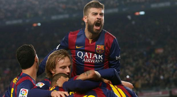 Barcelona's players (including Gerard Pique, at top) celebrate a goal