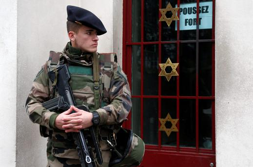 A heavily armed soldier guards a synagogue outside Paris