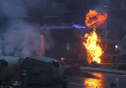 A police vehicle burns during a protest in Kosovo's capital Pristina.