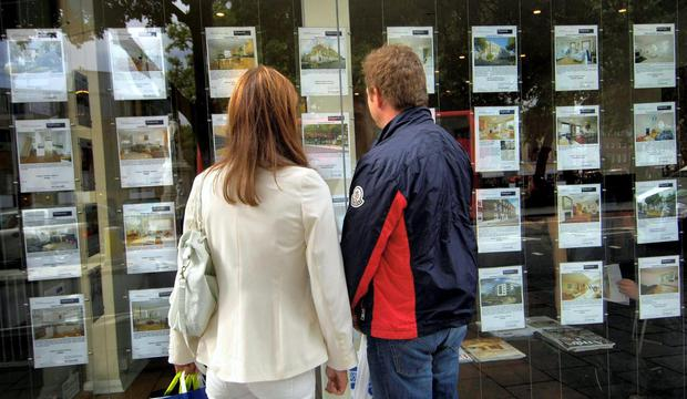 A couple look at their options outside an estate agent's window