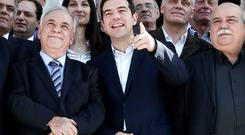 Greek Prime Minister Alexis Tsipras (C) gestures next to Deputy Prime Minister Yannis Dragasakis (L) and Interior and Administrative Reconstruction Minister Nikos Voutsis as the new government poses for a group picture after the first meeting of the new cabinet in the parliament building in Athens. Tsipras told his ministers on Wednesday voters had given them a mandate for radical change that would restore national sovereignty but pledged to negotiate responsibly with international creditors
