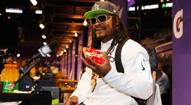 PHOENIX, AZ - JANUARY 27: Marshawn Lynch #24 of the Seattle Seahawks eats Skittles as he addresses the media at Super Bowl XLIX Media Day Fueled by Gatorade inside U.S. Airways Center on January 27, 2015 in Phoenix, Arizona. (Photo by Christian Petersen/Getty Images)