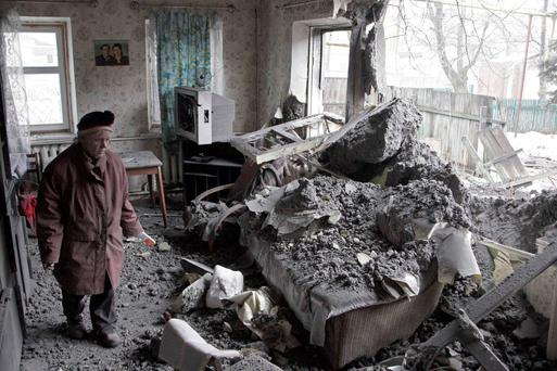 A woman surveys damage done to a house, which according to locals was recently damaged by shelling, in the suburbs of Donetsk