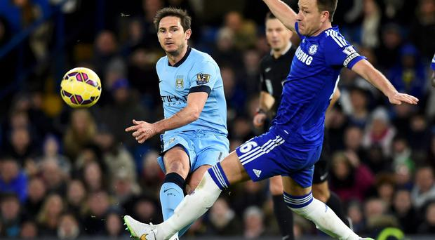Chelsea captain John Terry charges down a shot from his former colleague Manchester City's Frank Lampard