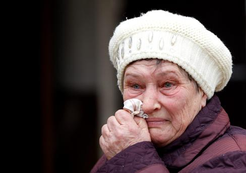 A woman wipes a tear outside of her home in the town of Svitlodarsk, Ukraineafter heavy shelling destroyed the local hospital, and damaged basic infrastructure, cutting off electricity, water and household gas supplies (AP Photo/Petr David Josek)
