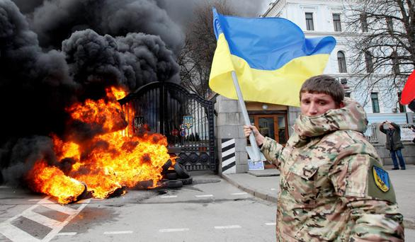 A serviceman from the battalion 'Aydar' waves a Ukrainian flag during a protest against the disbanding of the battalion, in front of Ukraine's Defence Ministry in Kiev