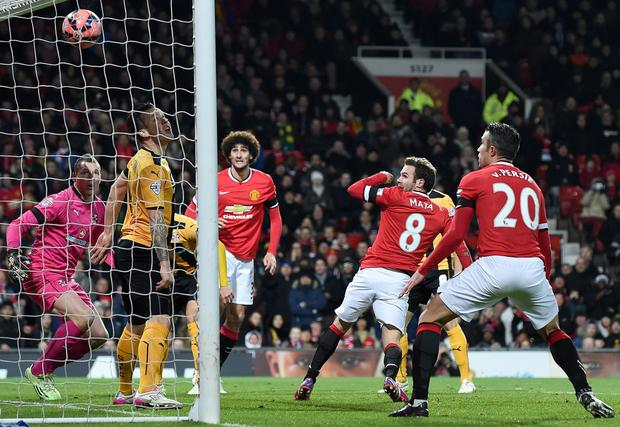 Manchester United's Spanish midfielder Juan Mata (3rd R) scores the opening goal of the FA Cup fourth round replay football match between Manchester United and Cambridge United at Old Trafford in Manchester, north west England, on February 3, 2015. AFP PHOTO / PAUL ELLIS == RESTRICTED TO EDITORIAL USE. No use with unauthorized audio, video, data, fixture lists, club/league logos or live services. Online in-match use limited to 45 images, no video emulation. No use in betting, games or single club/league/player publications. ==PAUL ELLIS/AFP/Getty Images