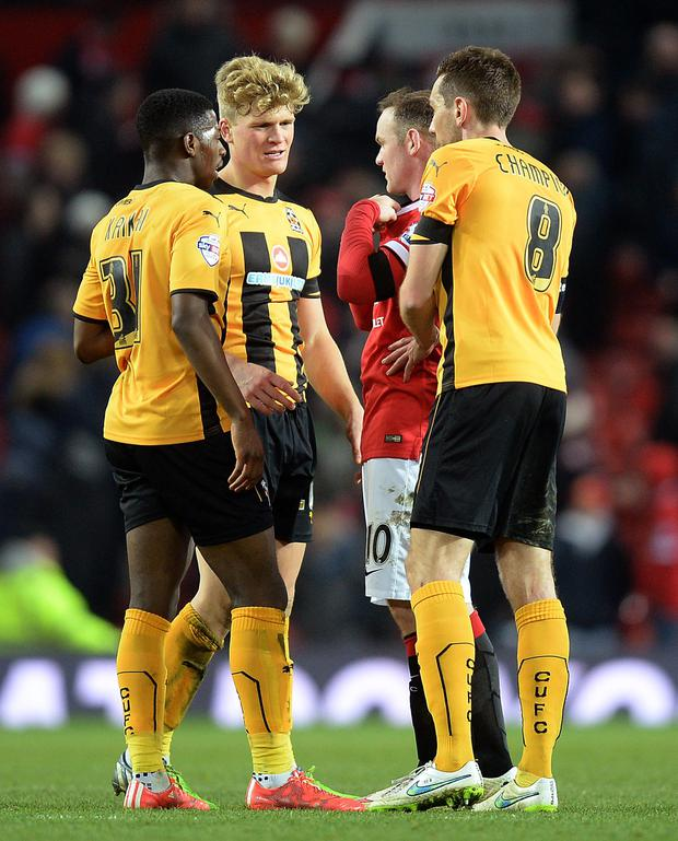 Cambridge United players ask for the shirt of Manchester United's Wayne Rooney after the FA Cup, Fourth Round replay at Old Trafford, Manchester. PRESS ASSOCIATION Photo. Issue date: Tuesday February 3, 2015. See PA story SOCCER Man Utd. Photo credit should read: Martin Rickett/PA Wire. RESTRICTIONS: Editorial use only. Maximum 45 images during a match. No video emulation or promotion as 'live'. No use in games, competitions, merchandise, betting or single club/player services. No use with unofficial audio, video, data, fixtures or club/league logos.