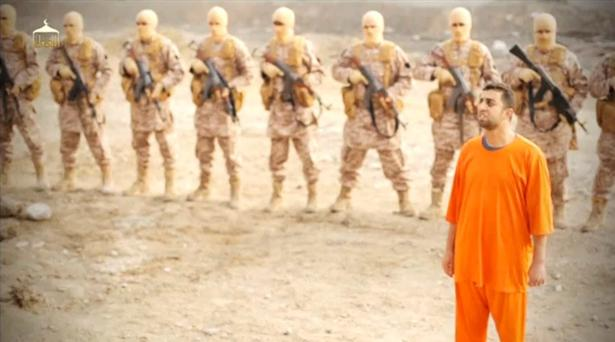 A man believed to be captured Jordanian pilot Muath al-Kasaesbeh stands in front of armed men in this still image from an undated video published on the internet yesterday that showed the pilot being burnt alive. Photo: Reuters