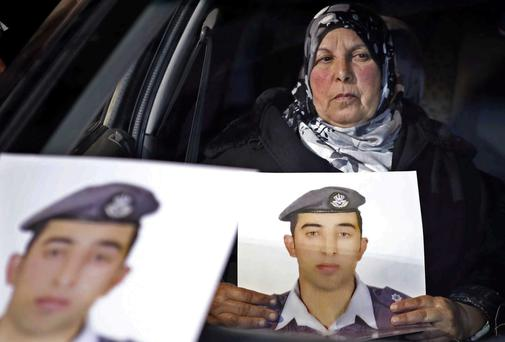 The mother of Jordanian pilot Lt. Mu'ath al-Kaseasbeh holds a picture of her son, who was burned alive by Isil. Photo: AP Photo/Raad Adayleh, File