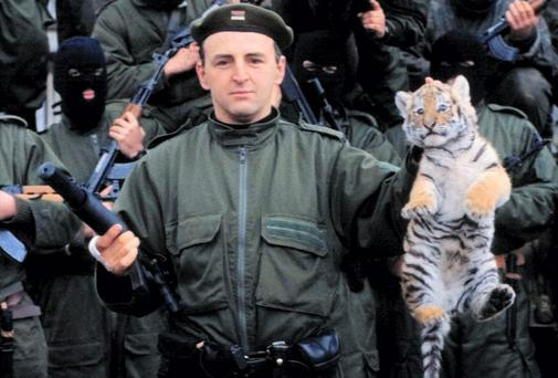 Notorious Serbian warlord Zeljko Raznatovic, aka Arkan, holding a tiger cub, symbol of his unit called Tigers, posing with his masked soldiers who blazed a trail to Croatia in 1991. Photo: AP PHOTO / Mioljub Jelesijevic
