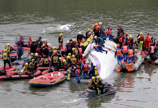 Rescuers carry out rescue operations after a TransAsia plane crashed into a river in New Taipei City, February 4, 2015. One person was killed but another 10 showed