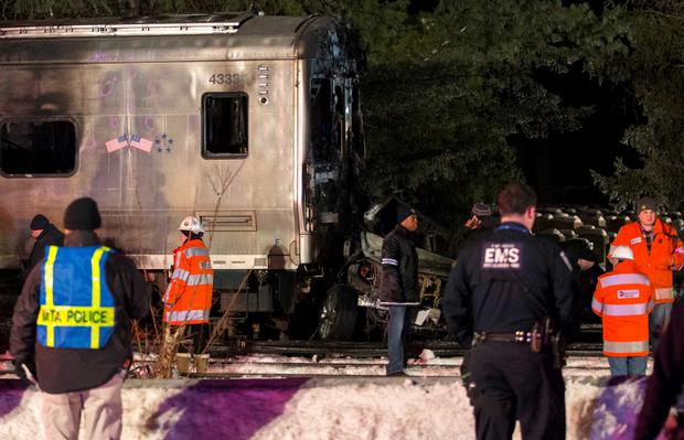 Emergency workers stand near a burned out Metropolitan Transportation Authority (MTA) Metro North Railroad commuter train that hit at least one car (C) near the town of Valhalla, New York, February 3, 2015. REUTERS/Mike Segar