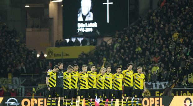 Borussia Dortmund's team lines up for a minute of silence for late former Bundesliga coach Udo Lattek before their German first division Bundesliga soccer match against FC Augsburg in Dortmund tonight