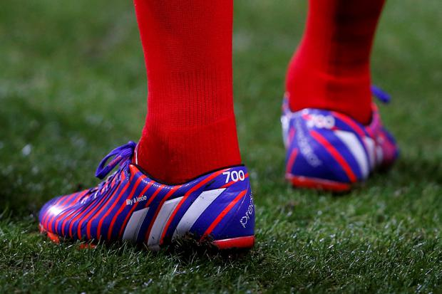 Liverpool's Steven Gerrard wears a specially-designed boot with the number 700 to match his number of games played for Liverpool, as he warms up prior to the match against Bolton Wanderers' during their FA Cup fourth round replay soccer match at the Macron Stadium in Bolton, northern England February 4, 2015. REUTERS/Andrew Yates (BRITAINSOCCER SPORT - Tags: SPORT SOCCER)