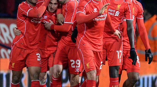 Philippe Coutinho (second from left) is congratulated by his Liverpool team-mates after scoring the winner in their 2-1 FA Cup fourth round replay victory over Bolton. Photo: Getty Images