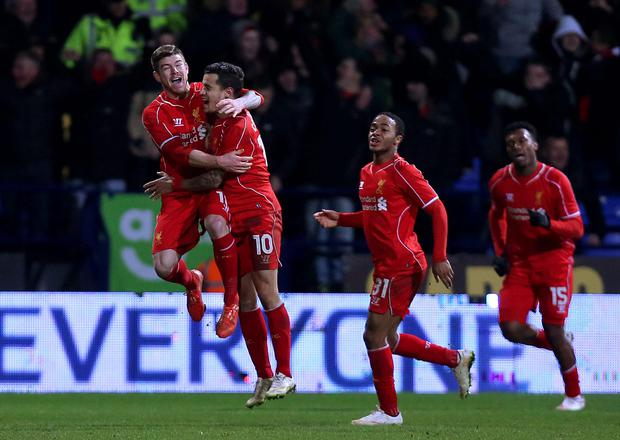 Liverpool's Philippe Coutinho (centre) celebrates with team-mates Alberto Moreno (left) and Raheem Sterling after scoring his side's second goal during the FA Cup Fourth Round Replay at the Macron Stadium, Bolton