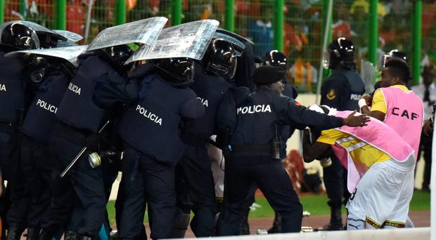 Ghana's national football team players leave the pitch protected by riot police at the half-time of the 2015 African Cup of Nations semi-final football match between Equatorial Guinea and Ghana in Malabo
