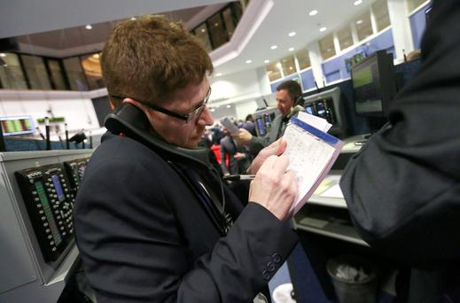 A trader makes notes whilst speaking on a telephone as he works on the trading floor outside the open outcry pit at the London Metal Exchange (LME) in London. Photo: Bloomberg
