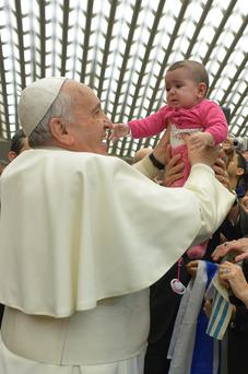 Pope Francis, pictured with a child at the Vatican, has sparked a row after he appeared to back a parents' right to smack a naughty child.