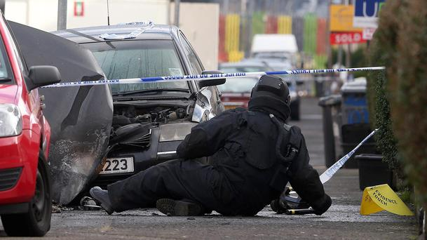 An Army technical officer examines a vehicle that was destroyed by a pipe bomb in West Belfast, Northern Ireland. A pipe bomb exploded under a car in St James Street late Wednesday in West Belfast and another device was found in North Belfast. Later a third suspicious device was found under a car in the markets area of Belfast