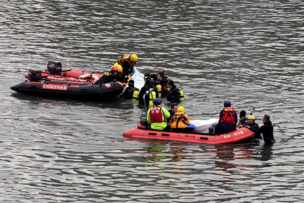 Emergency personnel retrieve two bodies of passengers who died in the TransAsia Airways Flight GE235 plane crash in New Taipei City February 6, 2015. REUTERS/Pichi Chuang