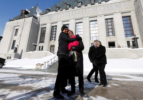 Lee Carter (2nd L) gets a hug from her husband Hollis Johnson outside the Supreme Court of Canada in Ottawa February 6, 2015. REUTERS/Chris Wattie