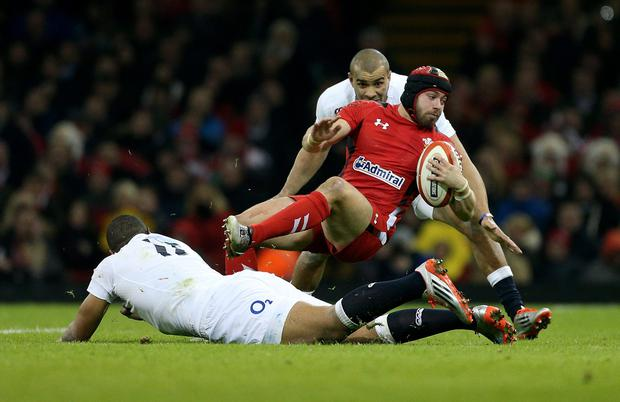 Wales Leigh Halfpenny is tackled by England's Luther Burrell and Jonathan Joseph during the RBS 6 Nations match at the Millennium Stadium, Cardiff. PRESS ASSOCIATION Photo. Picture date: Friday February 6, 2015. See PA story RUGBYU Wales. Photo credit should read: David Davies/PA Wire. RESTRICTIONS: Use subject to restrictions. Editorial use only. Strictly no commercial use. No use in books without prior written permission from WRU. Call +44 (0)1158 447447 for further information.
