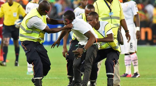 Security officers evacuate a supporter who made his way onto the pitch during the African Cup of Nations semi-final between Equatorial Guinea and Ghana. Photo: AFP PHOTO / ISSOUF SANOGOISSOUF SANOGO/AFP/Getty Images