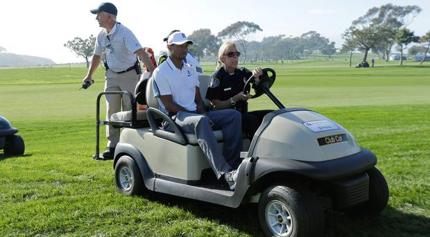 Tiger Woods is driven off the course after withdrawing from the Farmers Insurance Open in San Diego. Photo: AP Photo/Gregory Bull