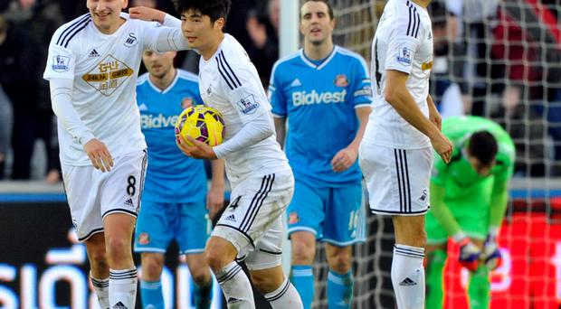 Swansea City's Ki Sung-Yueng (C) celebrates scoring a goal with Jonjo Shelvey (L) during their English Premier League soccer match at the Liberty Stadium in Swansea