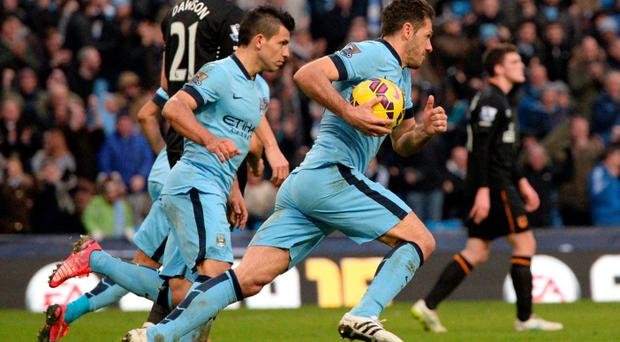 Manchester City's Argentinian striker Sergio Aguero (2L) and Manchester City's Argentinian defender Martin Demichelis (R) run back with the ball after Manchester City's English midfielder James Milner's goal