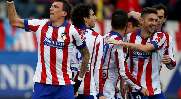 Atletico Madrid's Mario Mandzukic (L) celebrates after scoring his team's fourth goal against Real Madrid during their Spanish first division soccer match at the Vicente Calderon stadium in Madrid