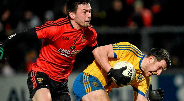Diarmuid Murtagh, Roscommon, evades the tackle of Damian Turley, Down, on his way to scoring his side's goal