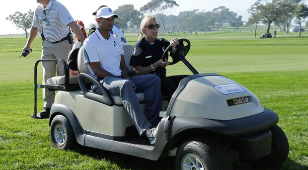 Tiger Woods is driven off the course in a cart after withdrawing during the first round of the Farmers Insurance Open
