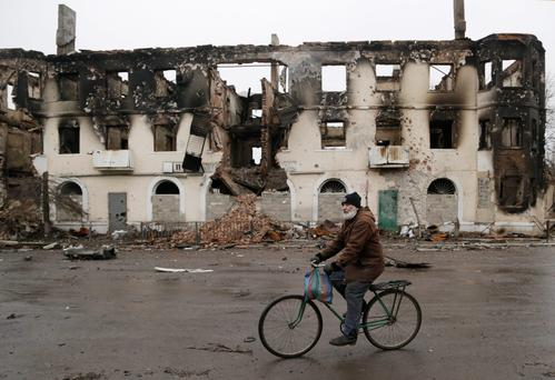 A resident rides his bicycle past a destroyed building in the town of Vuhlehirsk, Ukraine, as Vladimir Putin is expected to give his response today to the Franco-German plan for a Ukranian ceasefire (AP Photo/Petr David Josek)