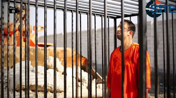 Jordanian pilot Muath al-Kaseasbeh standing in a cage just before being burned to death by his captors (AP Photo/SITE Intelligence Group)