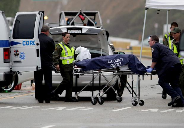 A Los Angeles County coroner worker loads a victim into a van at the scene of a four-car crash involving Olympic gold medalist and reality TV star Bruce Jenner in Malibu, California