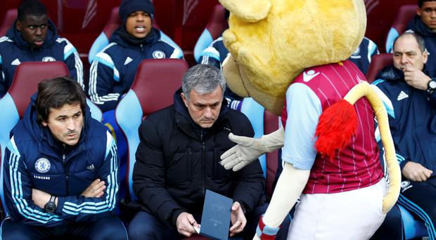 Chelsea manager Jose Mourinho reacts as the Aston Villa mascot extends his hand towards him before their English Premier League soccer match at Villa Park