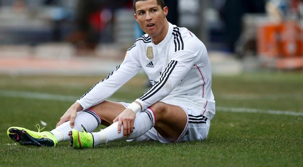 Real Madrid's Cristiano Ronaldo sits on the pitch during their Spanish first division soccer match against Atletico Madrid at the Vicente Calderon stadium in Madrid