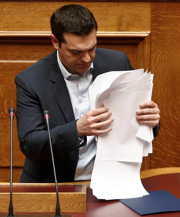 Greek Prime Minister Alexis Tsipras collects his notes following his first major speech in parliament in Athens February 8, 2015. REUTERS/ Alkis Konstantinidis