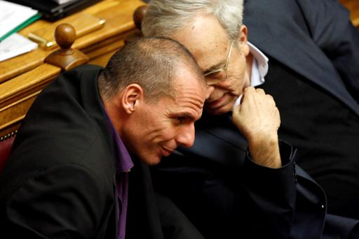 Greek Finance Minister Yanis Varoufakis (L) speaks with Greek Minister of Culture, Education and Religious Affairs Aristidis Baltas before the first major speech of Greek Prime Minister Alexis Tsipras in parliament in Athens February 8, 2015. REUTERS/ Kostas Tsironis