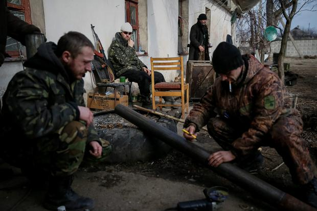 A Ukrainian serviceman rests as his comrades make a pipe for a wood stove near Debaltseve, eastern Ukraine. The leaders of Russia, Ukraine, Germany and France agreed to meet in Belarus on Wednesday to try to broker a peace deal for Ukraine amid escalating violence there and signs of cracks in the transatlantic consensus on confronting Vladimir Putin