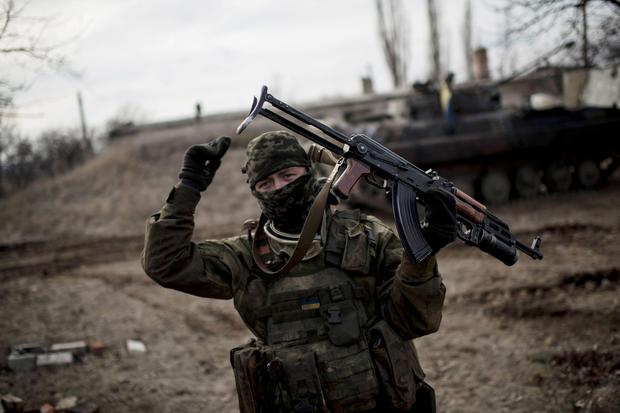 A Ukrainian soldier gestures as he guards territory near Debaltseve, eastern Ukraine. The government-held town of Debaltseve, a key railway junction, has been the epicenter of recent battles between Russian-backed separatists and Ukrainian government troops. For two weeks, the town has been pounded by intense shelling that knocked out power, heat and running water in the dead of winter