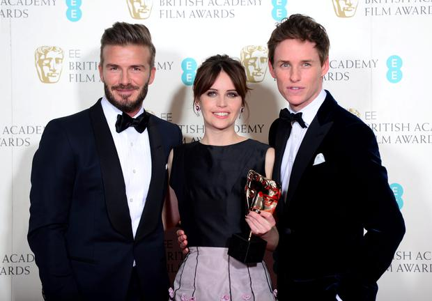 Eddie Redmayne and Felicity Jones alongside presenter David Beckham with the Outstanding British Film Award for The Theory of Everything