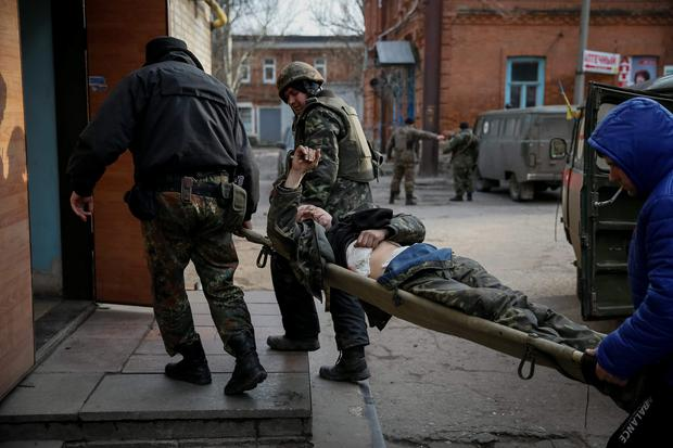 Ukrainian servicemen carry a wounded comrade into a hospital in Artemivsk. The leaders of Russia, Ukraine, Germany and France agreed to meet in Belarus on Wednesday to try to broker a peace deal for Ukraine amid escalating violence there and signs of cracks in the transatlantic consensus on confronting Vladimir Putin (REUTERS/Gleb Garanich)