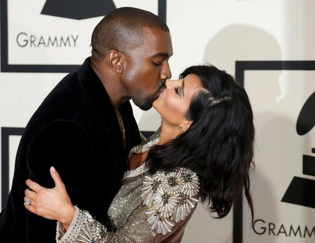 Kanye West and Kim Kardashian kiss on arrival at the 57th annual Grammy Awards in Los Angeles, California February 8, 2015