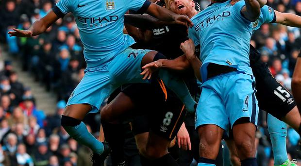 Fernandinho (L) and Vincent Kompany of Manchester City defend against Paul McShane and Tom Huddlestone of Hull City during the Barclays Premier League match between Manchester City and Hull City at the Etihad Stadium