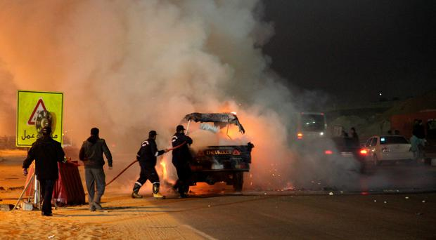 Egyptian firefighters extinguish fire from a vehicle outside a sports stadium in a Cairo's northeast district, on February 8, 2015 during clashes between supporters of Zamalek football club and security forces. Three people were killed and 20 injured, the health ministry said. The clashes erupted after fans tried to force their way into the venue to watch a game, the ministry said. AFP PHOTO / STRSTR/AFP/Getty Images